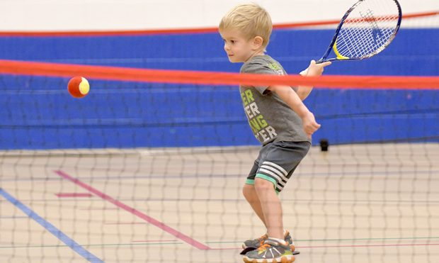 Young children playing tennis